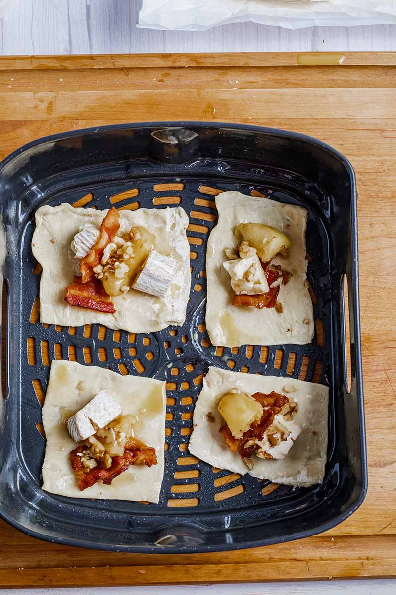 Air Fryer Peach Maple Bacon Brie Bites uncooked in the air fryer basket
