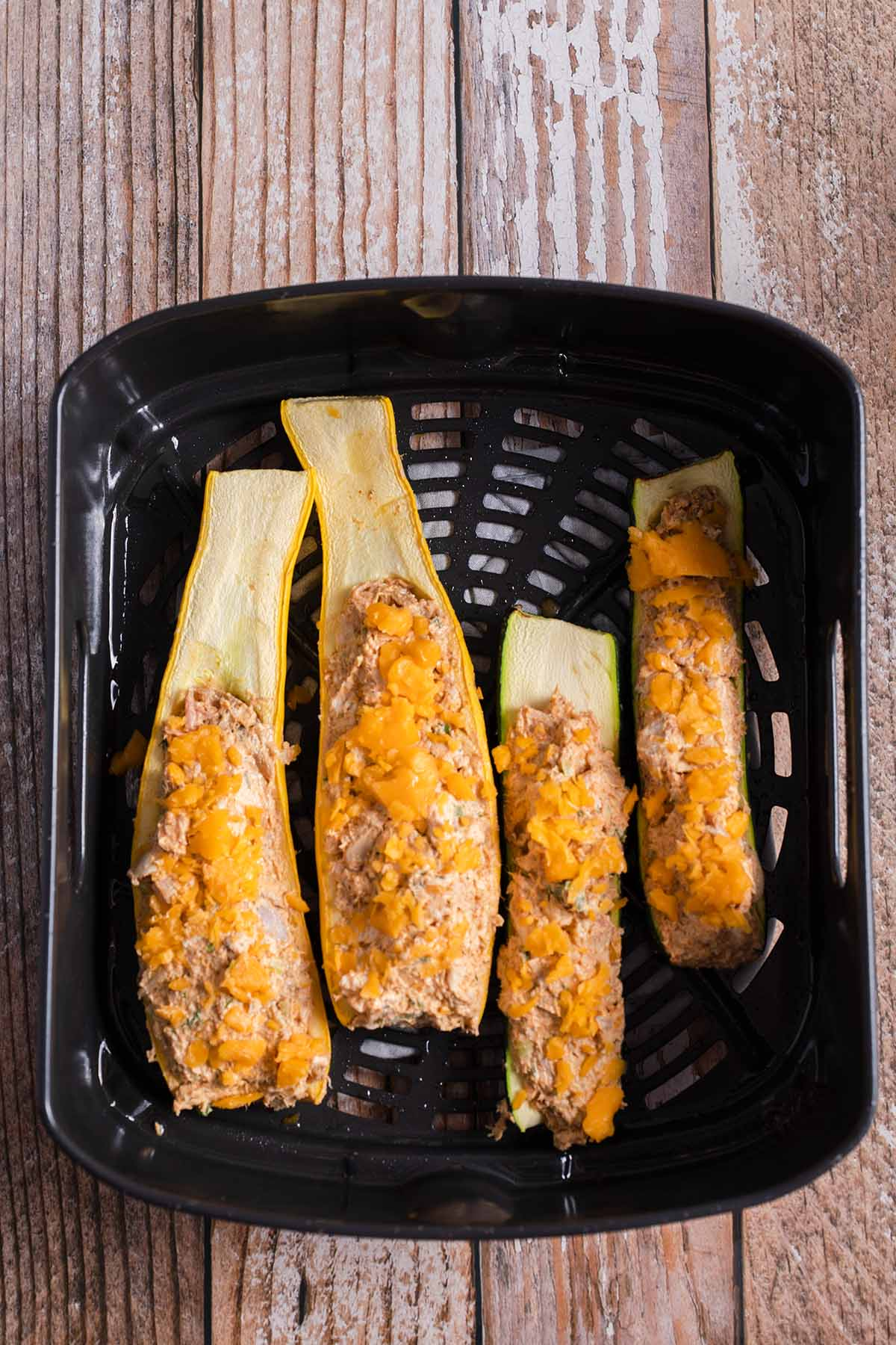 air fryer buffalo chicken zucchini boats  being cooked